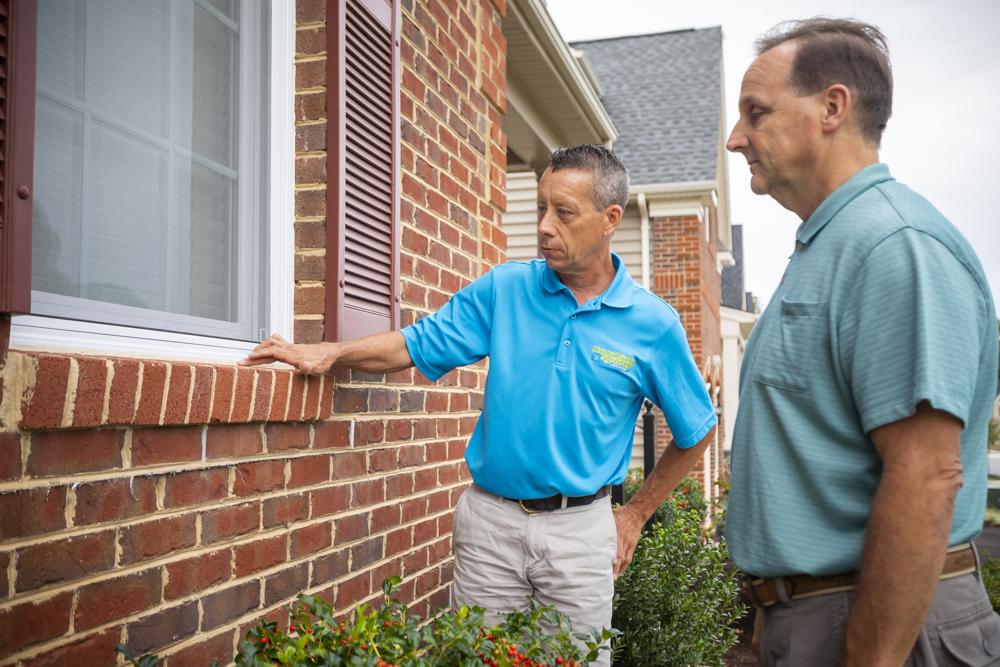 Natural Green pest control technician inspecting window