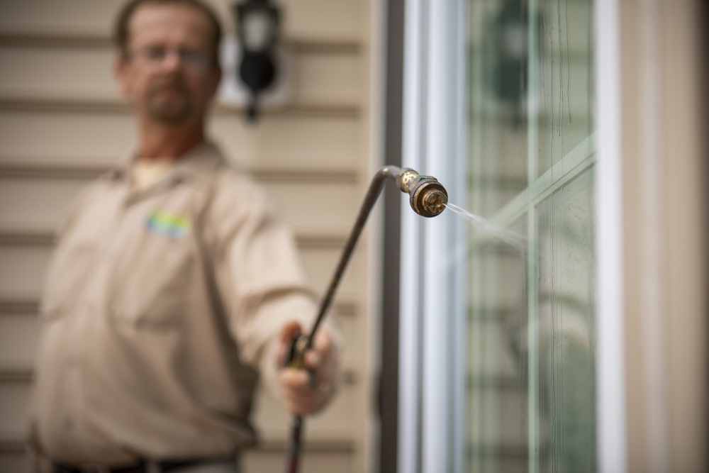 Pest control technician spraying for insects in Maryland